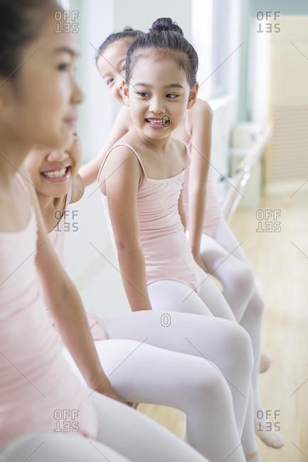 Little ballet dancers resting in dance studio