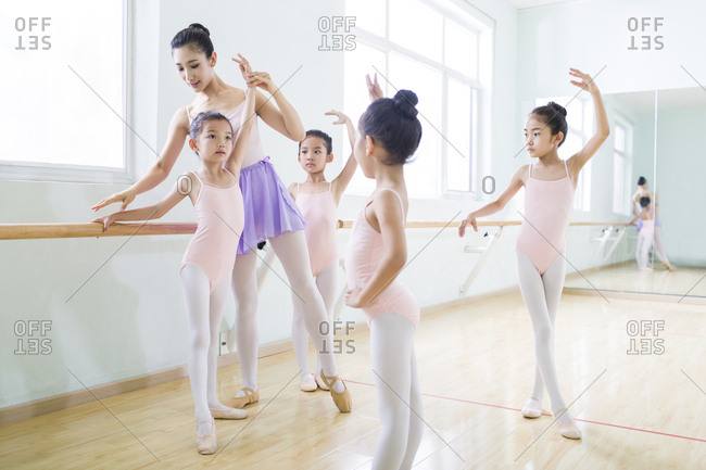 Young ballet instructor teaching girls in ballet studio