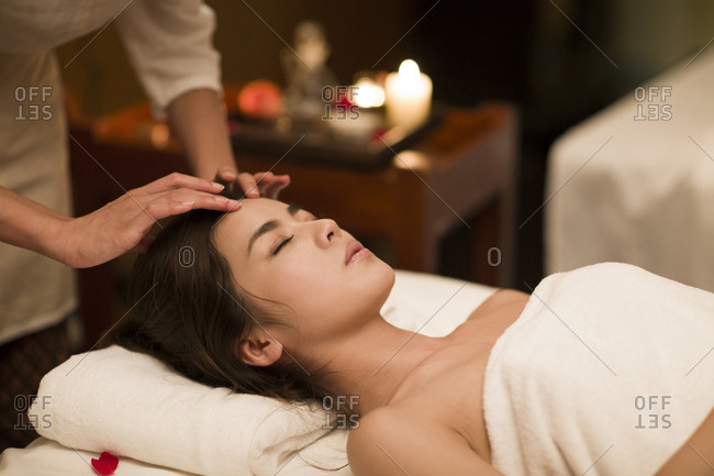 Young woman receiving facial massage at spa center