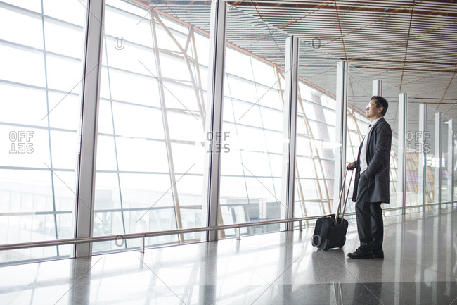 Businessman with wheeled luggage in airport lobby
