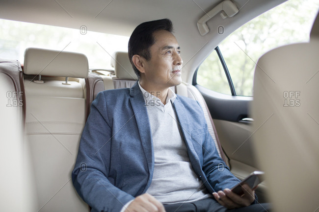 Businessman holding a smart phone inside car