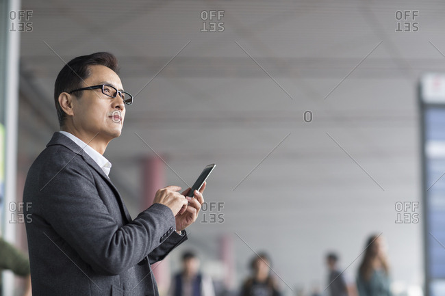 Businessman holding a smart phone in airport