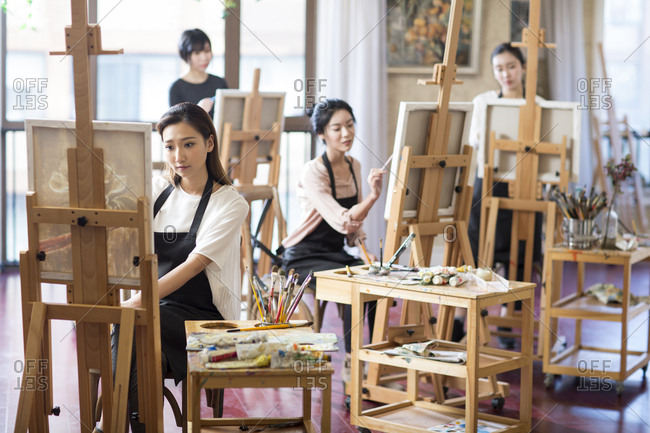 Young women painting in art class