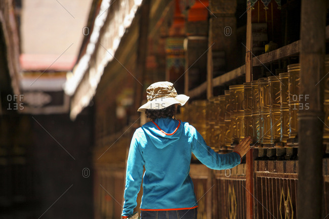 Tourist touching prayer wheel in Jokhang Temple