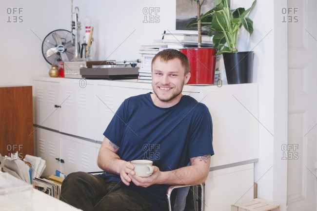 Portrait of happy businessman holding coffee cup while sitting in creative office