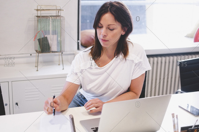 Businesswoman holding pen while reading book by laptop at desk in creative office