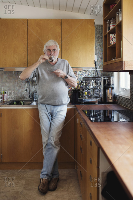 Full length of senior man drinking coffee while standing at kitchen