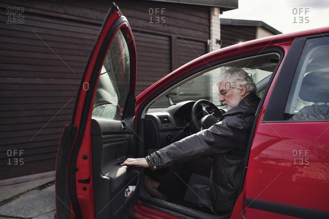 Senior man sitting in red car and closing door against garage