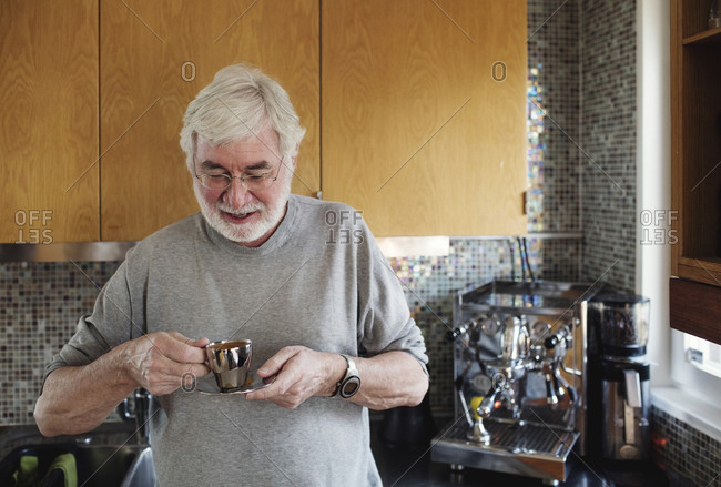 Smiling senior man holding coffee cup while standing at kitchen counter