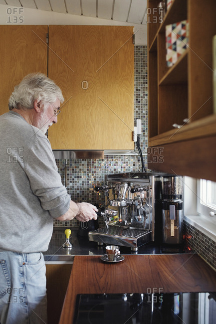 Senior man using coffee maker on kitchen counter at home