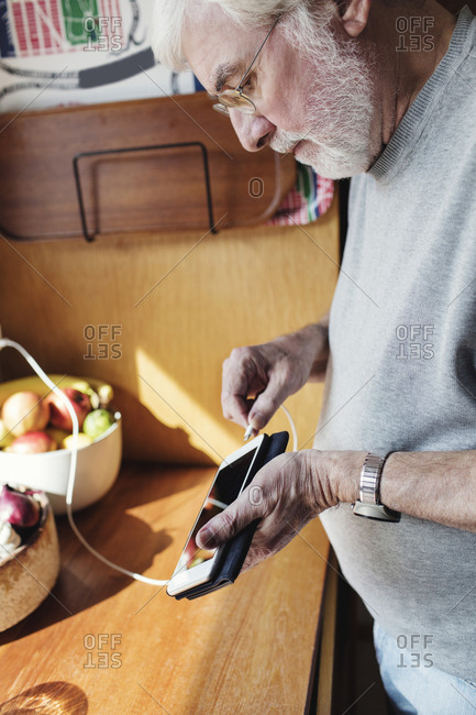 Senior man connecting cable to mobile phone at kitchen counter on sunny day