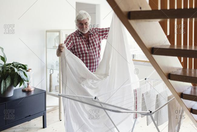 Senior man folding white sheet for drying on rack in living room