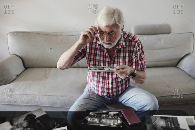 Senior man looking at vintage photographs while sitting on sofa at home
