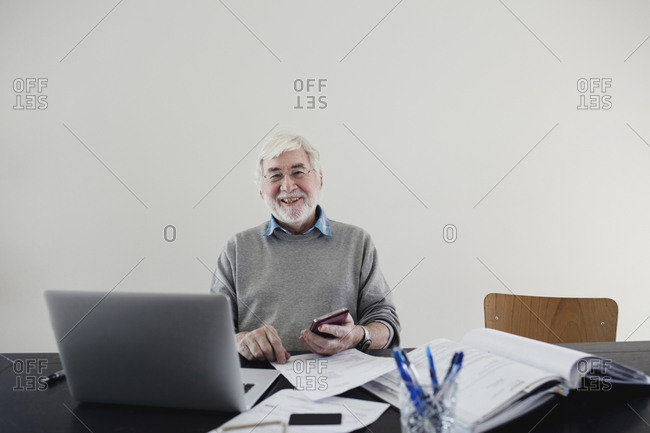Portrait of smiling senior man with laptop and bills sitting against white wall