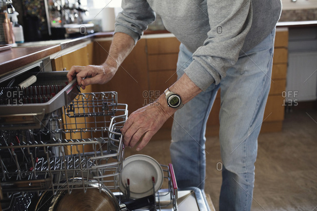 Midsection of senior man checking dishwasher at kitchen