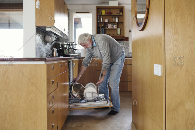 Senior man putting plates in dishwasher at kitchen