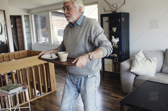 Senior man carrying serving tray while walking in living room at home