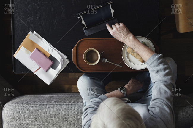 Directly above shot of senior man using digital tablet while having breakfast at home