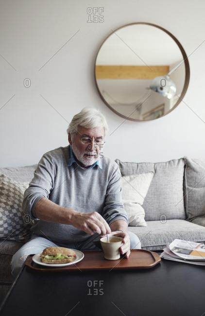 Senior man stirring tea while having breakfast at table in living room