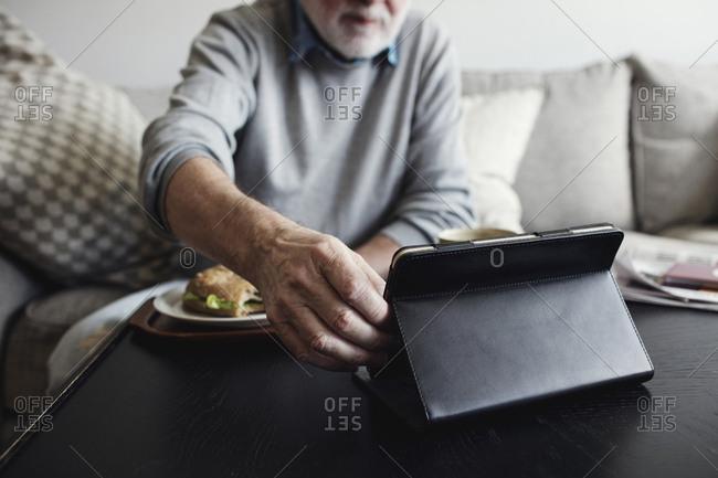 Senior man holding digital tablet while having breakfast at table