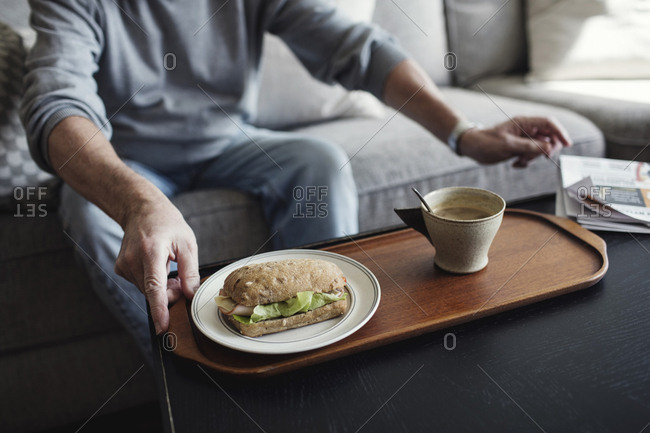 Midsection of senior man with sandwich and cup sitting on sofa at home