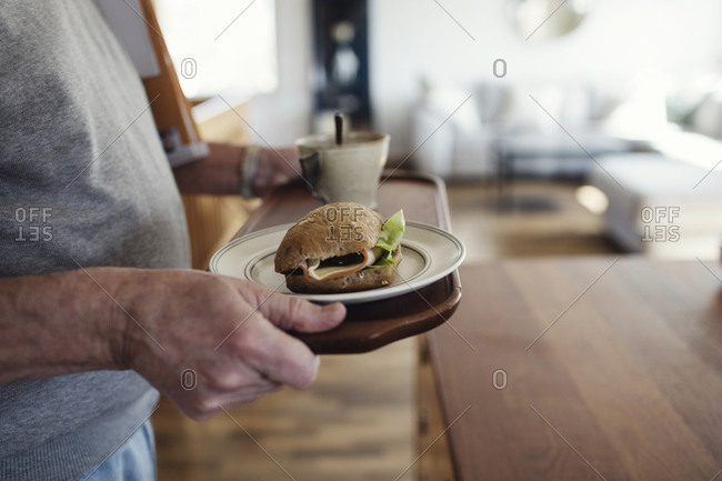 Midsection of senior man holding tray with sandwich and cup at home