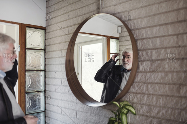 Senior man looking at mirror while standing in room