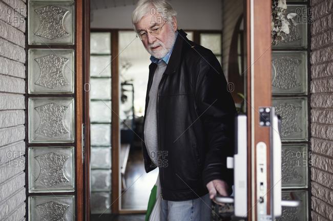 Senior man wearing leather jacket closing door