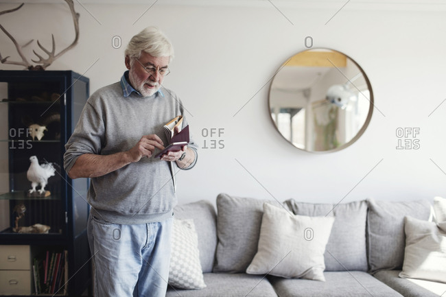 Senior man using mobile phone while standing by sofa at home
