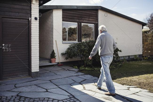 Full length of senior man walking towards house on sunny day