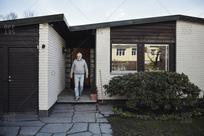 Senior man walking out of house against clear sky