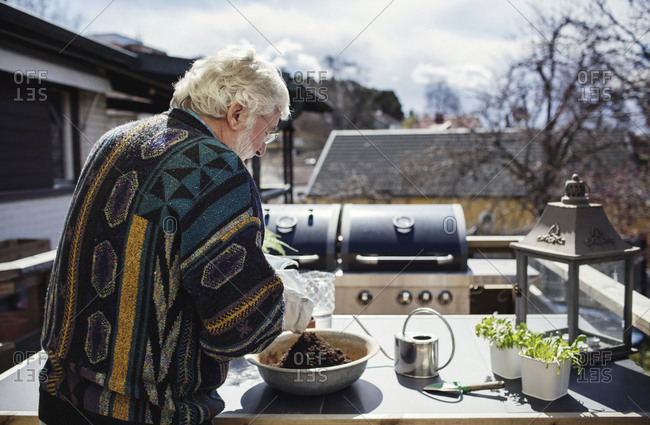 Senior man pouring fertilizer in container at table on sunny day