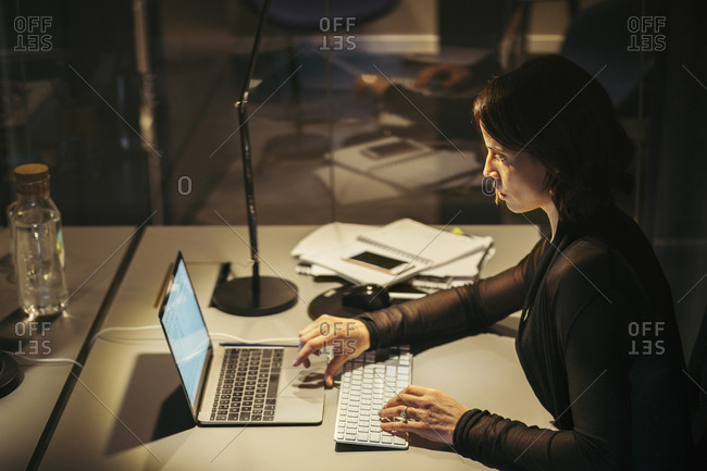High angle view of businesswoman using laptop at desk in office during night