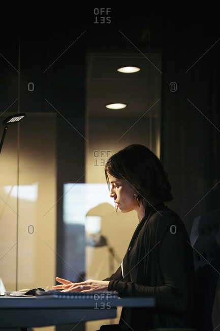 Profile view of serious businesswoman working at desk in dark office