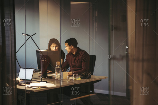 Business people discussing while working at desk in dark office