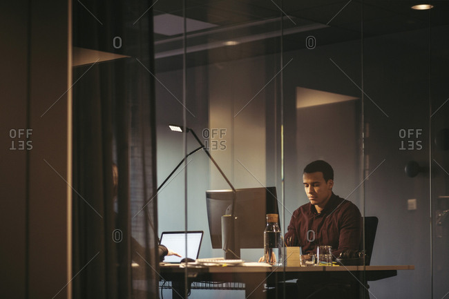 Businessman using computer at desk seen through glass in office