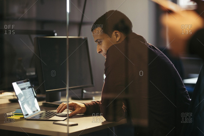 Businessman working on laptop at desk in office during night