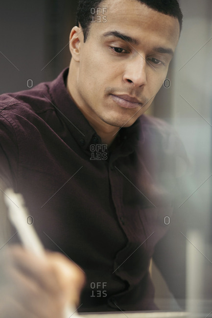 Businessman writing while sitting at desk in office