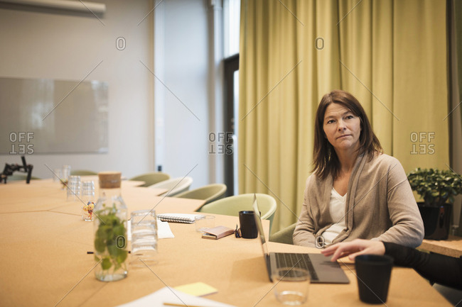 Serious businesswoman sitting with colleague at conference table in board room