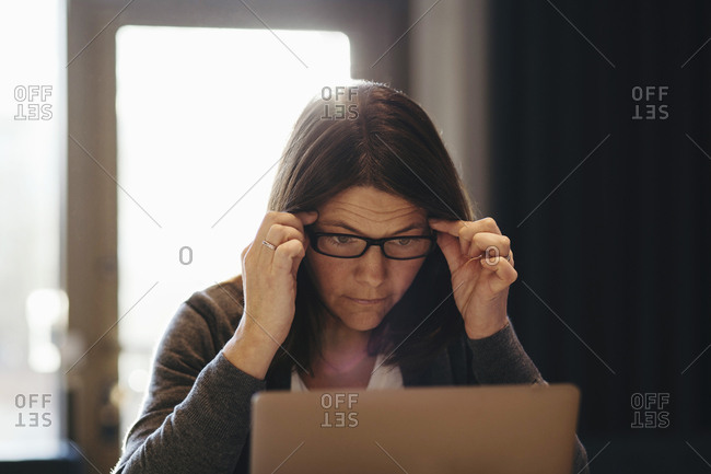 Mature businesswoman wearing eyeglasses while looking at laptop in office