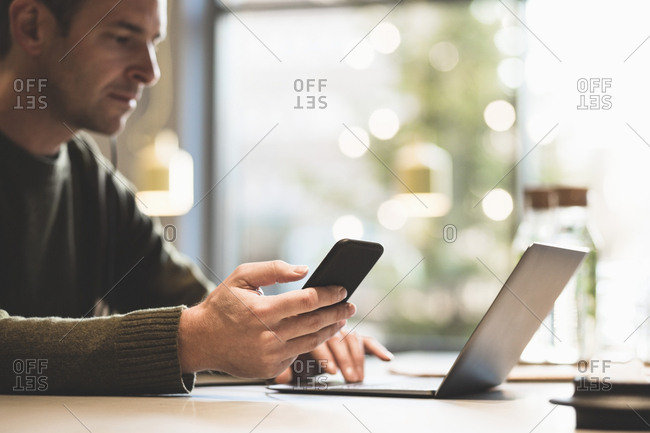 Serious businessman using mobile phone while using laptop at table in office