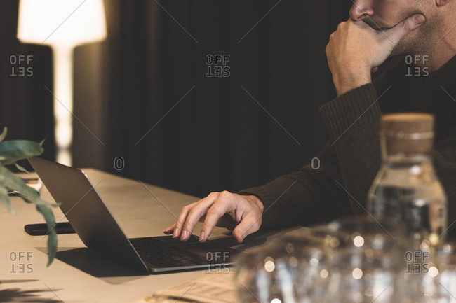 Cropped image of thoughtful businessman using laptop at desk in office