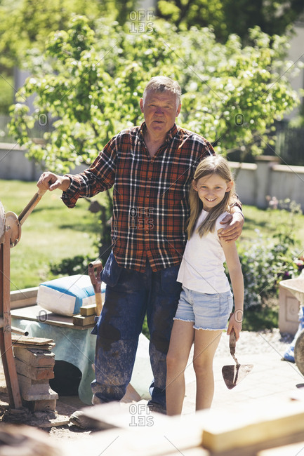 Portrait of grandfather and granddaughter standing by cement mixer in yard