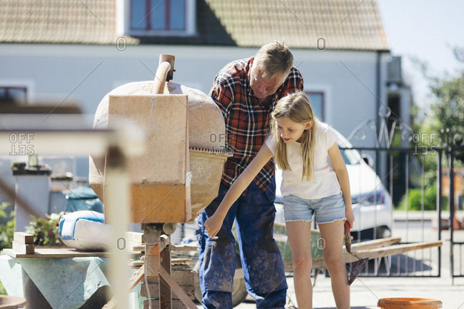 Grandfather using cement mixer with granddaughter in yard