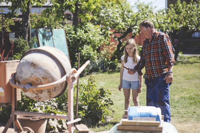 Grandfather giving shovel to granddaughter while standing by cement mixer in yard