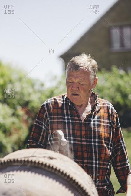 Senior man looking at cement mixer at yard