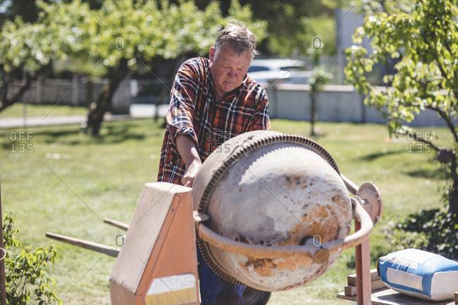 Senior man using cement mixer at yard