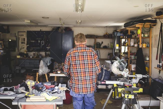 Rear view of senior man standing in workshop