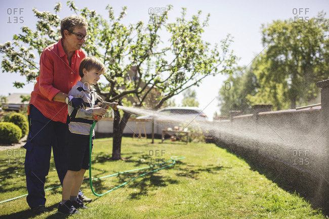 Full length of grandmother assisting grandson in spraying water on surrounding wall at yard