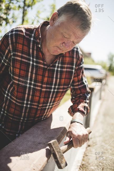 Senior man examining surrounding wall with hammer at yard